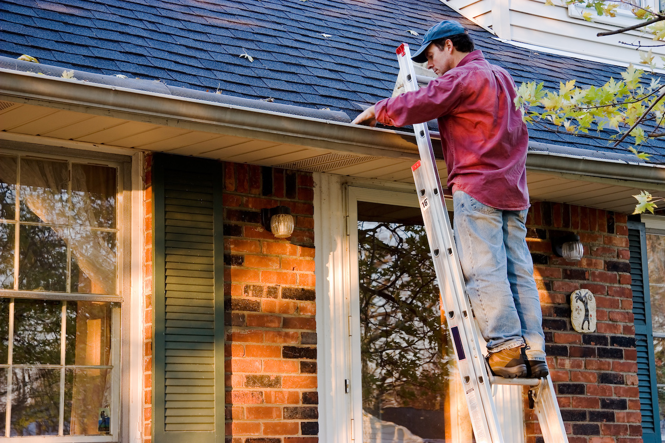 Man preparing his Kelowna home for fall by cleaning gutters